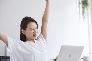 ノートパソコンを使い部屋で仕事をする女性の写真素材 [FYI04889451]