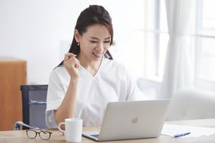 ノートパソコンを使い部屋で仕事をする女性の写真素材 [FYI04889454]