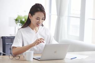 ノートパソコンを使い部屋で仕事をする女性の写真素材 [FYI04889455]