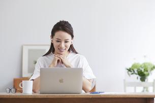 ノートパソコンを使い部屋で仕事をする女性の写真素材 [FYI04889458]