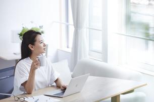ノートパソコンを使い部屋で仕事をする女性の写真素材 [FYI04889579]