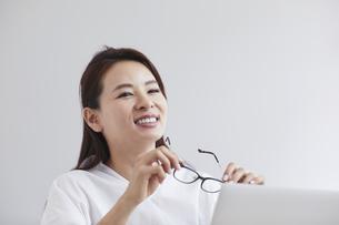 ノートパソコンを使い部屋で仕事をする女性の写真素材 [FYI04889580]