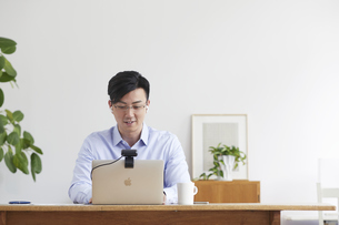 イヤホンをしながらオンライン会議をする男性の写真素材 [FYI04889583]