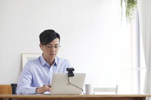 イヤホンをしながらオンライン会議をする男性の写真素材 [FYI04889585]