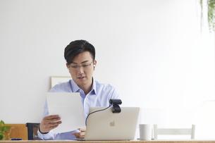 イヤホンをしながらオンライン会議をする男性の写真素材 [FYI04889586]