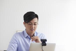 イヤホンをしながらオンライン会議をする男性の写真素材 [FYI04889589]