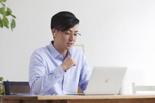 イヤホンをしながらオンライン会議をする男性の写真素材 [FYI04889591]