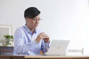 イヤホンをしながらオンライン会議をする男性の写真素材 [FYI04889594]