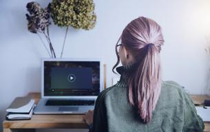 ノートパソコンで動画再生する女性の後ろ姿のテクノロジーイメージの写真素材 [FYI04889682]