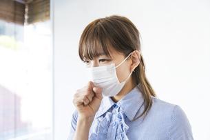 マスクをして咳をする女性の写真素材 [FYI04889932]