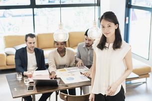 オフィスでポーズをするビジネスウーマンと国際色豊かなビジネスチームの写真素材 [FYI04891284]