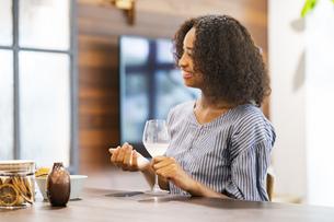 ワイングラスを手に笑顔で談笑する若い女性の写真素材 [FYI04891286]