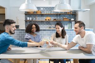 ダイニングテーブルで談笑する女性たちと男性たちの写真素材 [FYI04891302]