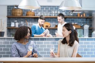 ダイニングテーブルで談笑する女性たちと男性たちの写真素材 [FYI04891304]