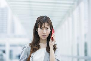 困った表情で電話するビジネスウーマンの写真素材 [FYI04891328]