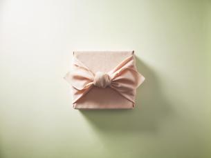 ピンク色の風呂敷に包まれた贈答品イメージの写真素材 [FYI04892645]