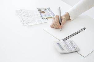 電卓,小銭,レシートを横に置きペンでノートに記入する女性の手のクローズアップの写真素材 [FYI04892670]