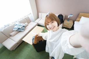 ホテルの部屋で自撮り写真(セルフィー)を撮る女性の写真素材 [FYI04892745]