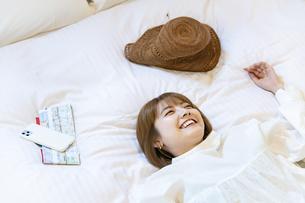 ホテルのベッドでゆったりする女性の写真素材 [FYI04892746]