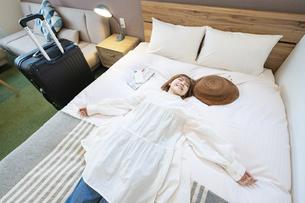 ホテルのベッドでゆったりする女性の写真素材 [FYI04892748]