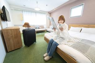 ホテルの部屋で地図とスマートフォンを見る女性の写真素材 [FYI04892753]