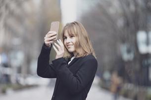 街でスマートフォンを使う女性の写真素材 [FYI04893153]