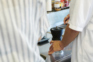 コーヒー豆を挽く男性の写真素材 [FYI04894977]