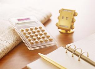 電卓と新聞と手帳の写真素材 [FYI04895385]