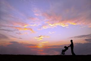 夕日の空を背景にベビーカーを押し散歩をする若い男性の写真素材 [FYI04895869]
