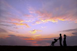 夕日の空を背景にベビーカーを押し散歩をする若い夫婦の写真素材 [FYI04895874]
