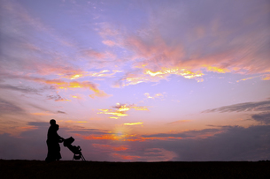 夕日の空を背景にベビーカーを押し散歩をする若い夫婦の写真素材 [FYI04895879]