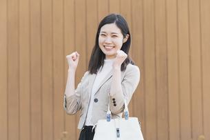 屋外で笑顔を見せるオフィスカジュアルスタイルの女性の写真素材 [FYI04896291]