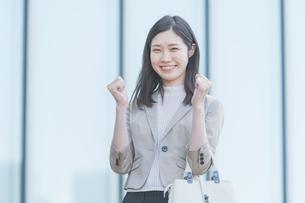 屋外で笑顔を見せるオフィスカジュアルスタイルの女性の写真素材 [FYI04896299]