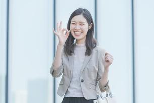 屋外で笑顔を見せるオフィスカジュアルスタイルの女性の写真素材 [FYI04896305]