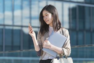 スマートフォンを触るビジネスウーマンの写真素材 [FYI04896330]