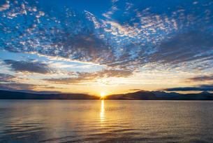 十和田湖大川岱園地付近より日の出と朝焼けに染まる空にご来光映す十和田湖八甲田方面の山並みの写真素材 [FYI04897282]