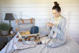ベッドの上で旅行の支度をしながらスマホを見ている女性の写真素材 [FYI04897929]