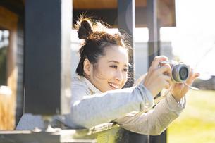 カメラで写真を撮っている笑顔の女性の写真素材 [FYI04897936]