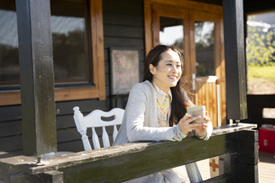 コテージのポーチでお茶を飲んでいる笑顔の女性の写真素材 [FYI04897943]