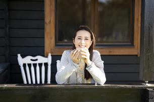 コテージのポーチでお茶を飲んでいる笑顔の女性の写真素材 [FYI04897946]