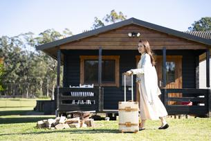 スーツケースを引いてコテージの前を歩いている女性の写真素材 [FYI04897950]