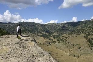 山岳地帯の景色を眺めるウズベク人の老人の後姿の写真素材 [FYI04898080]