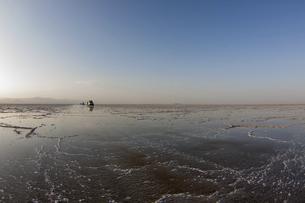 真っ平らで何もないカルム塩湖を走る車列の写真素材 [FYI04898089]