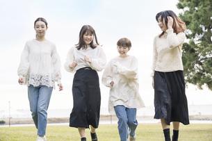 笑顔で話しながらゆっくり走る女性4人の写真素材 [FYI04899601]