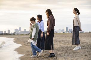 夕暮れの中、海沿いで遊ぶ若い女性4人の写真素材 [FYI04899609]
