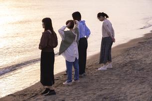 夕暮れの中、海沿いで遊ぶ若い女性4人の写真素材 [FYI04899613]