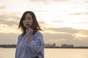夕方、海をバックに撮影された若い女性のポートレートの写真素材 [FYI04899627]