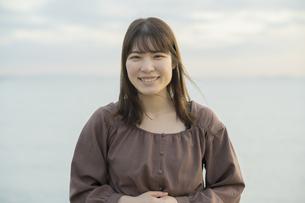 夕方、海をバックに撮影された若い女性のポートレートの写真素材 [FYI04899630]