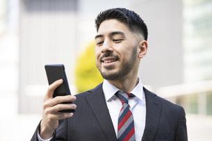 スマートフォンを使うビジネスマンの写真素材 [FYI04899714]
