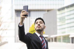スマートフォンを使うビジネスマンの写真素材 [FYI04899720]